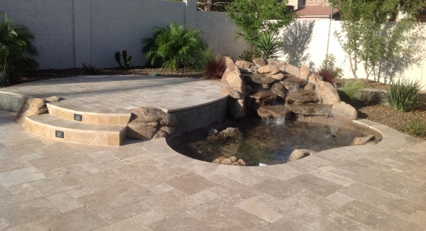 The patio is a popular spot for Glendale, AZ water features. If it's not recirculating into the swimming pool, then you need a waterfall pond design. This one is on the edge of a raised area of the patio to give it a more natural look.