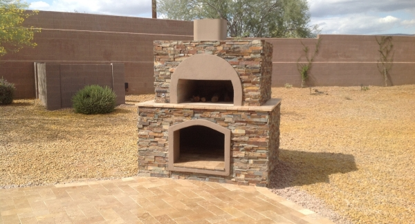 This wood-fired pizza oven Anthem clients requested is designed to match their new stone outdoor kitchen island that sits a little farther right. The lower wood box keeps fuel handy and dry.