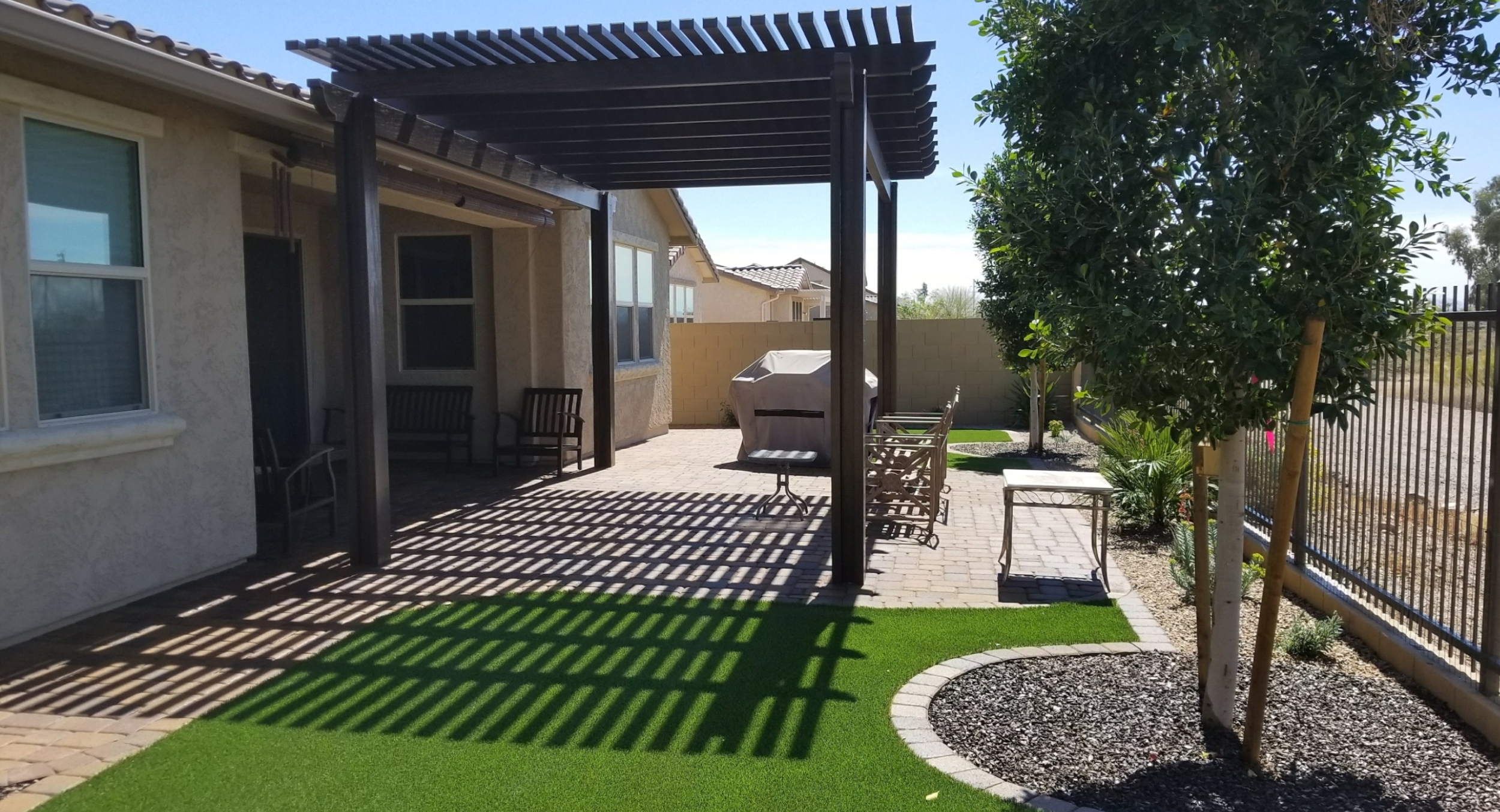 This slice of a backyard turned into a lovely space with landscape design. Glendale, AZ clients now have a lush look with synthetic lawn, shade ramada over a new travertine patio, and new shade trees and flowering desert plants.