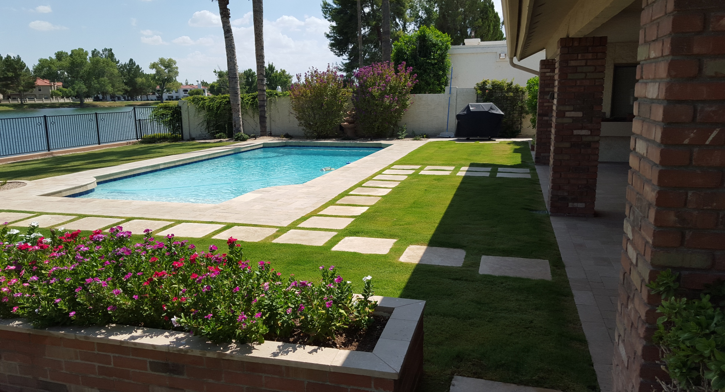Refresh your older pool with gorgeous landscape design. Paradise Valley homeowners had us remove dated landscaping and pool decking, replacing it with desert bred sod and travertine stepping stones and pool deck.