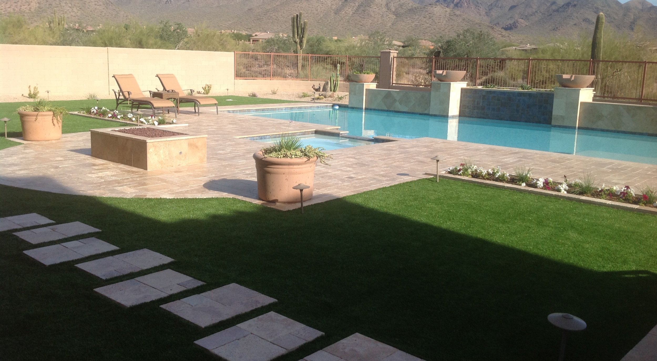 The everything in your yard available Phoenix landscaper, Scottsdale, NW Valley too. This travertine pool deck, fire pit and synthetic lawn is all our work.