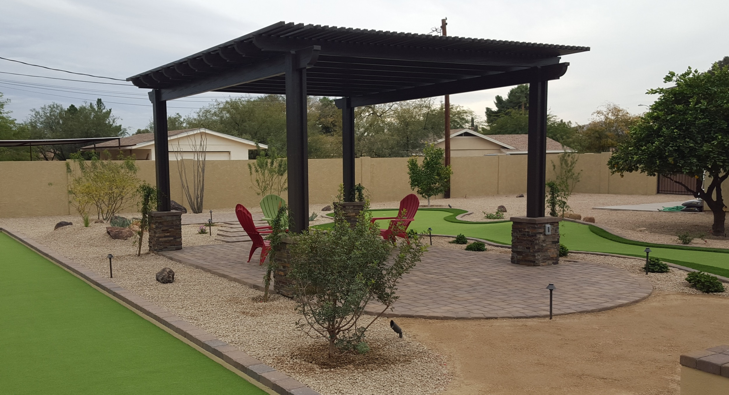 Phoenix-Scottsdale landscapers you can rely on for high quality installation, like this putting green and fire pit under a shade structure.