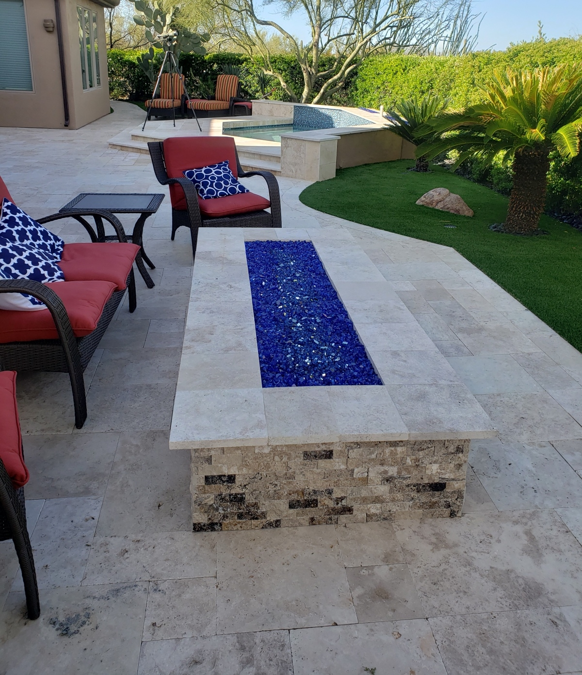 Cobalt Fire Glass adds lots of pizzazz to this travertine fire pit and spa surround. The spa has it's own channel fire pits too.