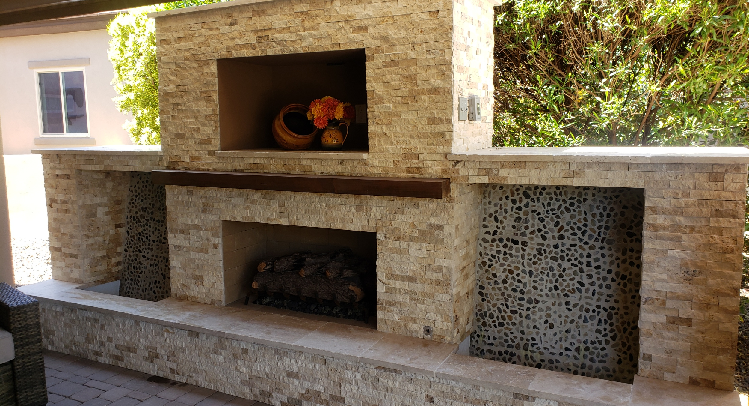 Split-face travertine outdoor fireplace. Peoria, AZ client's had us add twin water wall water features on each side, plus an outdoor TV cabinet above the hearth.