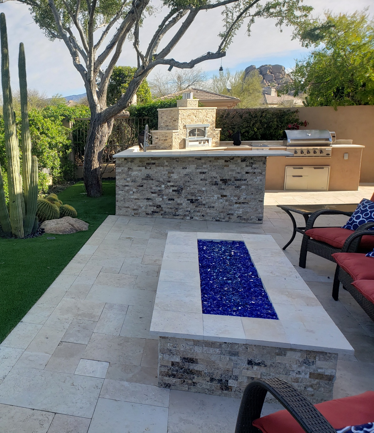 Smooth and split-face travertine create a beautiful outdoor fire pit and outdoor kitchen. Scottsdale clients also included a pizza oven in the new outdoor kitchen.