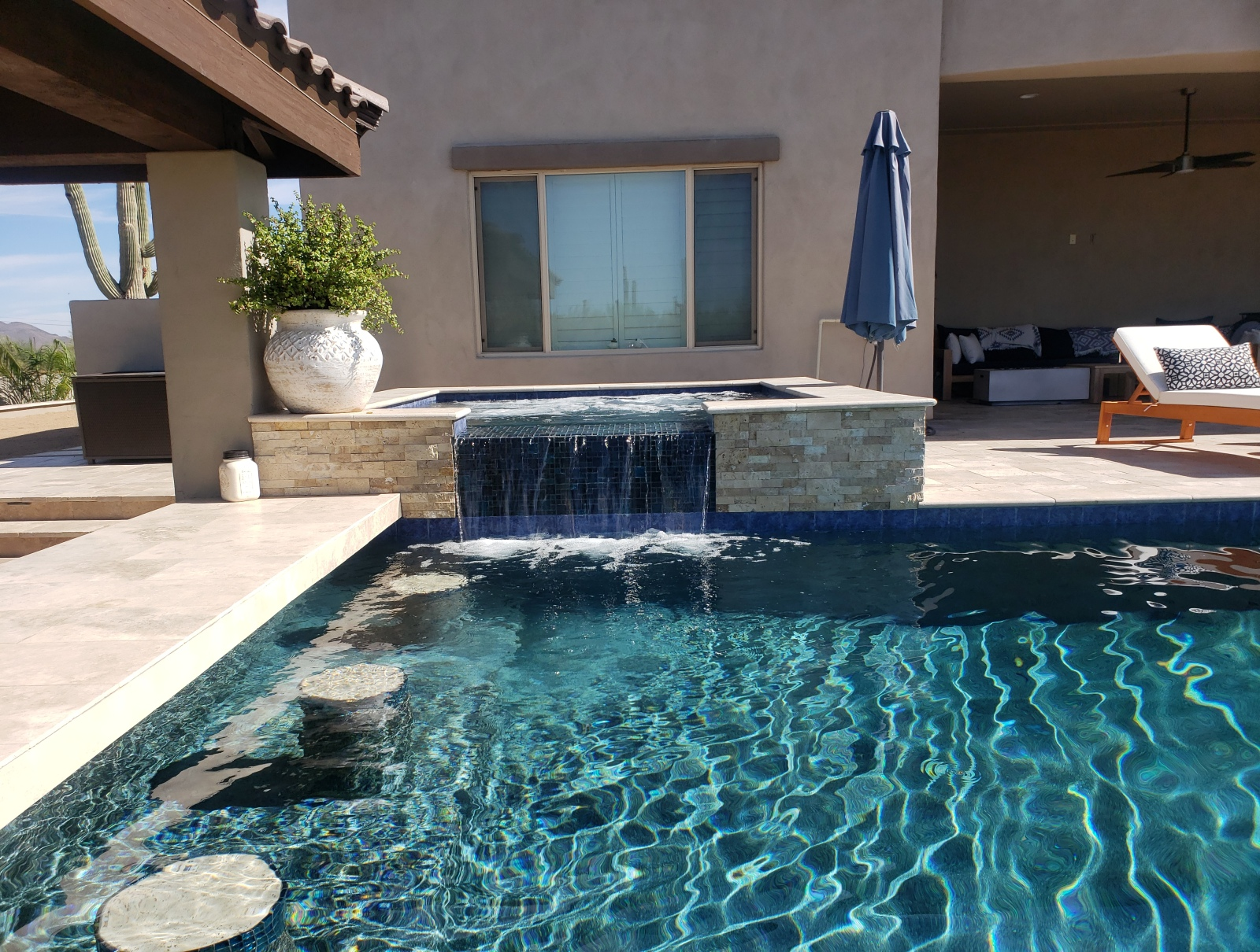 Midnight blue tiled spa spill-over doubles as a waterwall water feature at the end of the 3-stool swim bar. Another beautiful project by Desert Crest, pool builders - Phoenix, AZ.